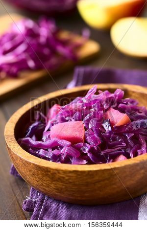 Braised red cabbage with apple in wooden bowl with ingredients in the back photographed with natural light (Selective Focus Focus one third into the image)