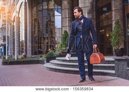 Confident businessman is going out from home with luggage. He is holding newspaper and looking forward with aspiration