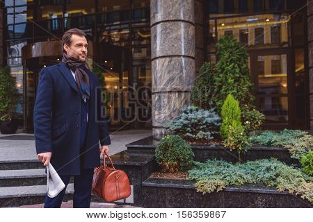 Man is ready for business trip. He is standing near building and looking forward with anticipation. Man is carrying baggage and newspaper