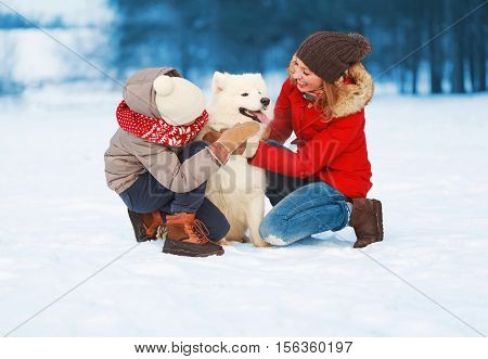 Christmas Happy Smiling Family, Mother And Son Child Walking With White Samoyed Dog On Snow In Winte