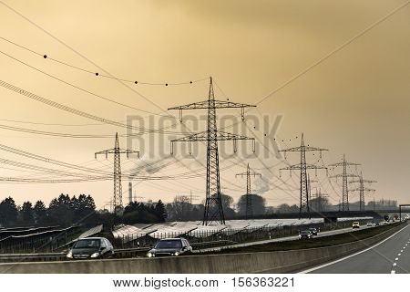 german highway in the evening with solar power field and electric pylons in background under dramatic sky