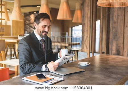 Cheerful man is resting after work in cafe. He is reading newspaper and drinking coffee. Man is sitting and smiling