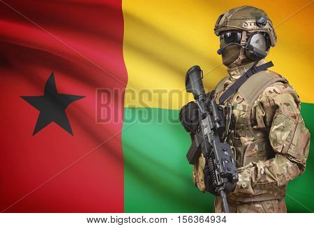 Soldier In Helmet Holding Machine Gun With Flag On Background Series - Guinea-bissau