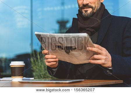Happy businessman is reading newspaper with relaxation in cafeteria outdoors. He is smiling