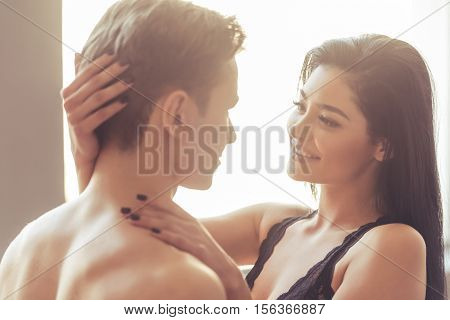 Sensual young couple is looking at each other passionately and smiling