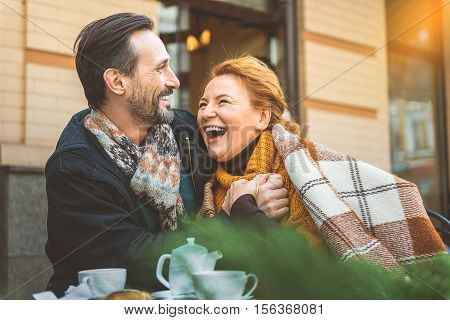 Happy middle-aged couple is relaxing in cafeteria outdoors. They are hugging with love and laughing