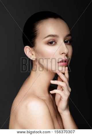 Beautiful woman headshoot portrait over dark background touching her chin. Sexy lips with natural beige lipstick makeup.