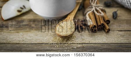cinnamon stick and a tablespoon of brown sugar on wooden background, holiday concept and warm mood