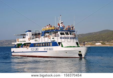 RHODES, GREECE - JULY 13, 2016: Ferry boat Nissos Halki docking at the port of Kamiros Skala on the Greek island of Rhodes. The ferry is one of several operating between Rhodes and Halki island.
