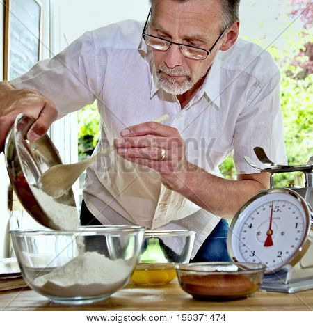 Mature Man Learning To Make A Chocolate Cake