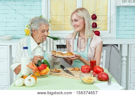 Girl cook a pizza in the kitchen she offers her mom eat.