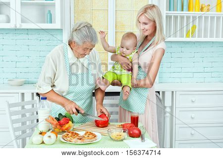Grandma prepares food and at this time mother with a child watching her.