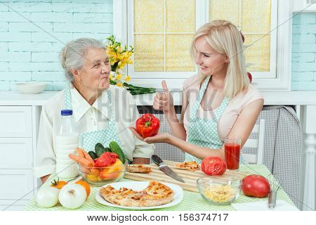 Girl advises her grandmother vegetarian food pizza.
