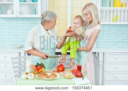 Grandma feeds the child vegetarian food standing next to mother.