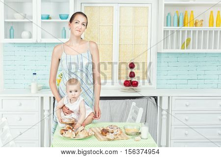 In the kitchen standing at a table mother and her daughter.