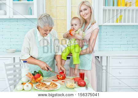 Young girl holds her baby near her old mother preparing food in the kitchen.