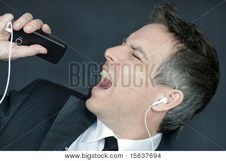 Businessman Wearing Headphones Sings Into Cell Phone