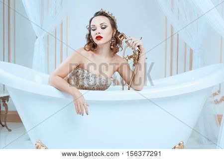 Queen sitting in a bathtub with a crown on his head.