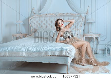 Queen sitting on a bed in a luxurious bedroom.