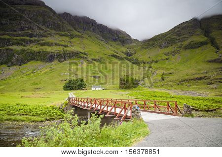 Achnambeithach cottage and a bridge at the mountain edge in Glencoe Scottish Highlands