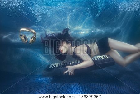 Girl swims with piano under water in the pool.