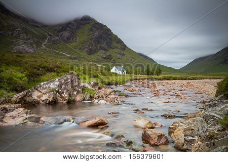 White cottage at the banks of the river Coe Glencoe Scotland