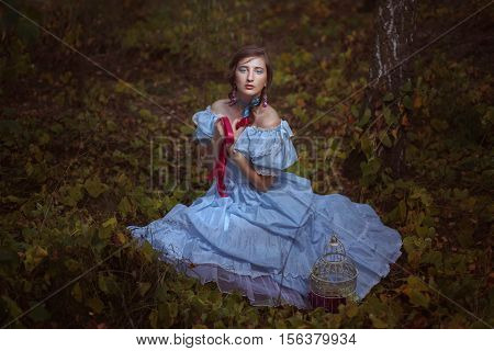 oung girl in retro outfit sitting on the grass in the forest.