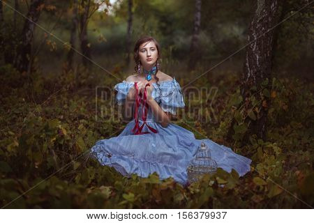 Young girl with red ribbon in hands sitting on the grass in the forest.