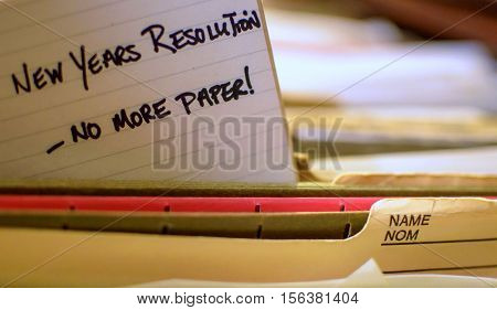 Office New Year Resolution Handwritten Note in Filing Cabinet to go paper free organize paper and go paper free selective focus with words