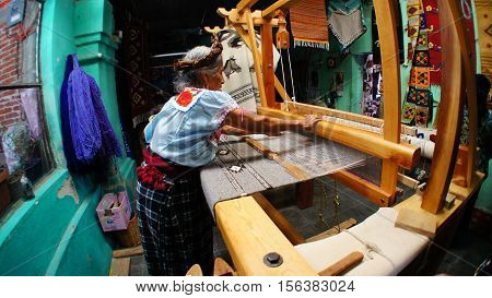 Mexican woman is waving a tapetes (rugs) on hand-operated looms from locally-produced wool and dyes.