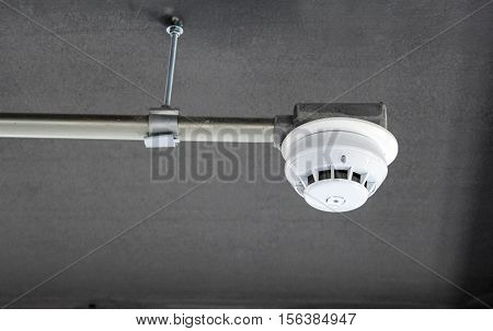 Smoke detector alarm with white pipe installed