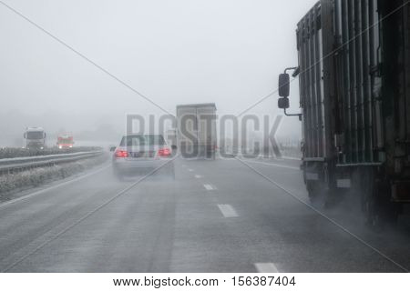 cars trucks and a rescue vehicle driving in dangerous winter weather with poor visibility during snow and rain on the highway concept for safety in traffic copy space