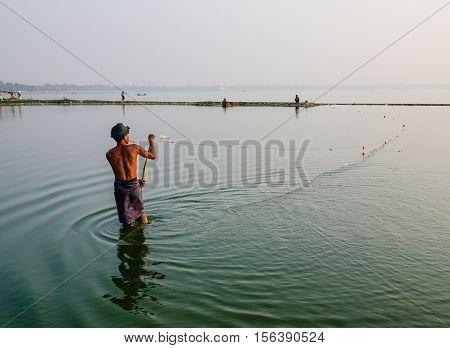Burmese Man Catching Fish On Lake