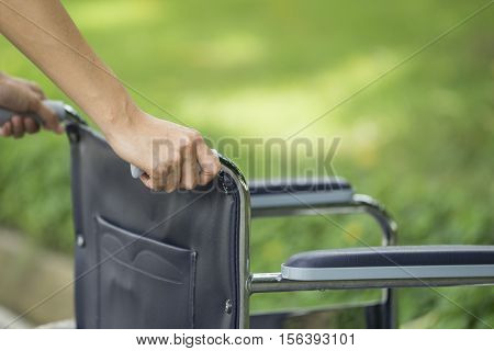 Empty wheelchair pushed by nurse's hands, close up