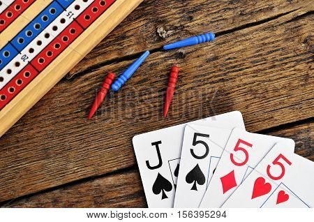 A top view image of a wooden cribbage board with cribbage pegs and cards.