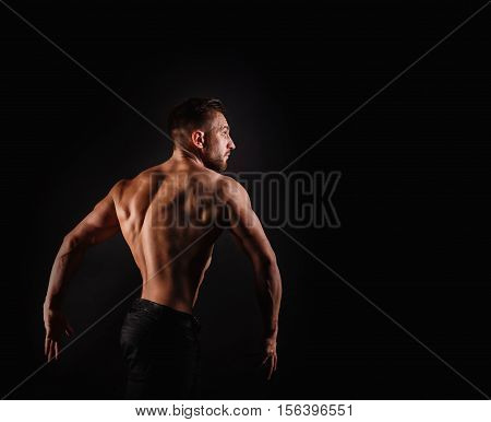 Bodybuilder posing on a black background. Dramatic portrait of an athlete. Drying. Relief and sculptural muscles of the body. Concept of healthy lifestyle. Dorsi muscle.