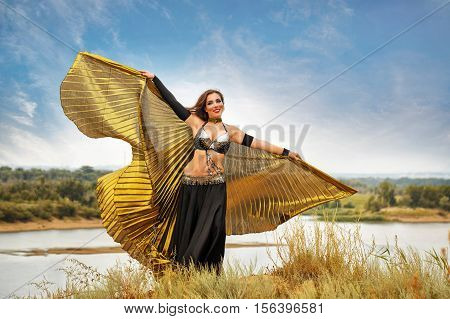 Oriental Beauty dance with wings. Nice girl in national dress dancing in the open air. Nomads. Beauty and grace.
