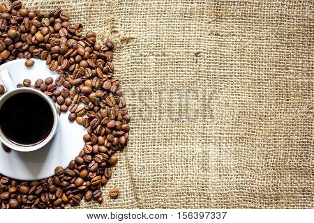 coffee beans with coffe cup on linen cloth background top view.