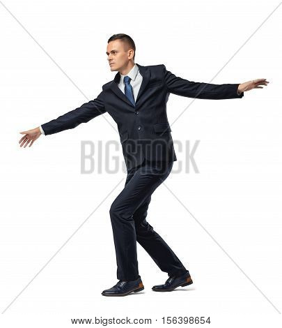 Fully concentrated businessman walking a tightrope or border, isolated on a white background. Keeping balance. Acting carefully. Being very cautious. Concentration and attention.