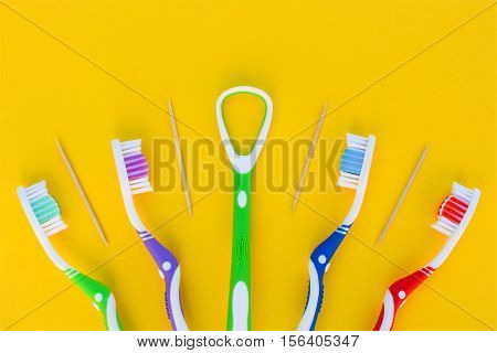 Toothbrushes, toothpick, tongue scraper on yellow background. Top view.