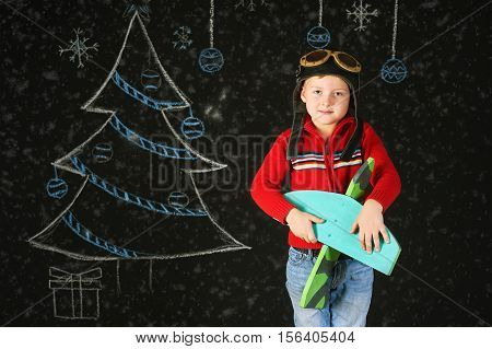 a handsome boy with a wooden toy plane , a retro helmet on a background with a painted tree