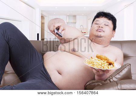 Obesity person watching tv while sitting on the sofa and holding junk food at home