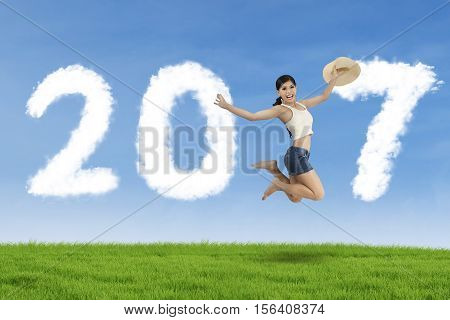 Image of young woman holding hat and dancing on the meadow while forming numbers 2017 with cloud