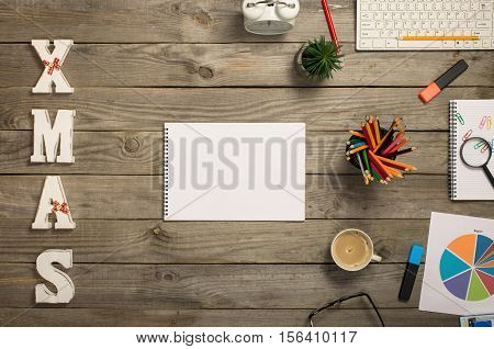 Notepad with blank pages with cup of coffee chart keyboard pencils plant and word xmas on the wooden desk top view