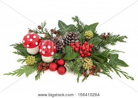 Christmas decorative display with red baubles and fly agaric mushroom decorations, holly, ivy, snow covered pine cones and winter greenery over white background.