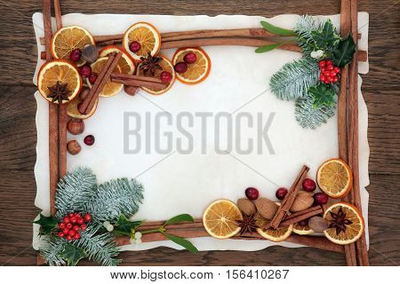 Christmas abstract background border with cinnamon sticks, spices, cranberries, dried orange fruit, holly, ivy mistletoe and fir on parchment paper over oak wood.