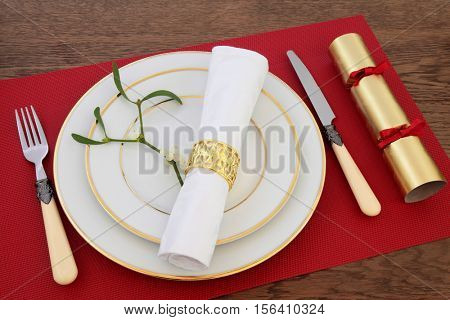Christmas dinner table setting with white porcelain plates, antique cutlery, linen serviette and ring, mistletoe and cracker on red place mat over oak background.