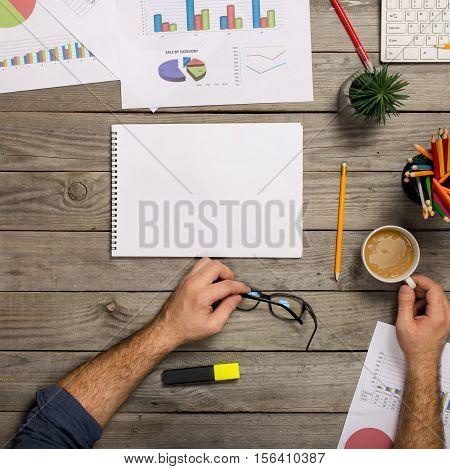 Man working behind office wooden desk top view.