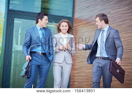 Group of cheerful business people leaving office building