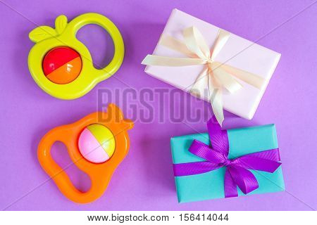 birth of baby - gift box on purple background top view